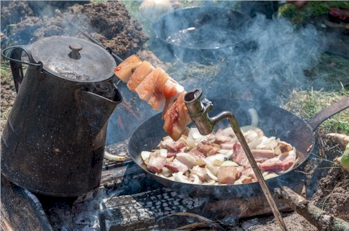 Civil war camp fire with fatback speared on bayonet and bacon frying in the pan.